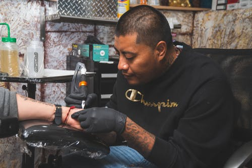Man Wearing Black Shirt Tattooing A Person