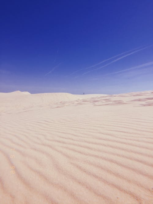 Low Angle Shot Of White Desert Sands Under Clear Blue Skies