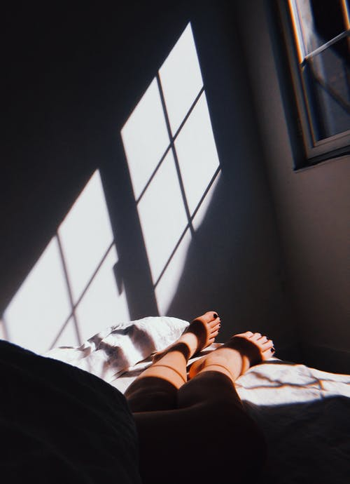 Person Lying On Bed Inside Room
