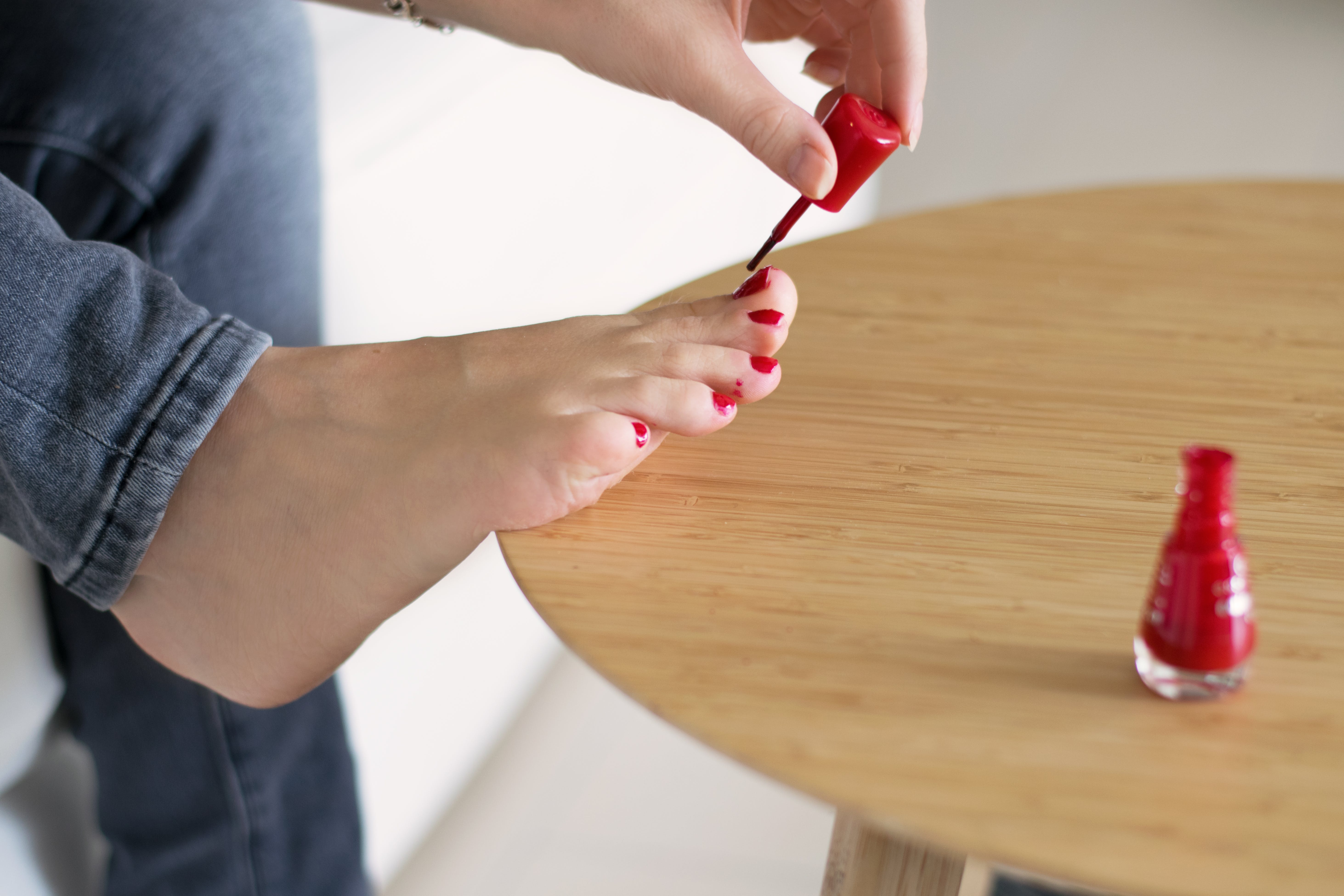 Person Polishing Its Foot Nails Using Red Polisher