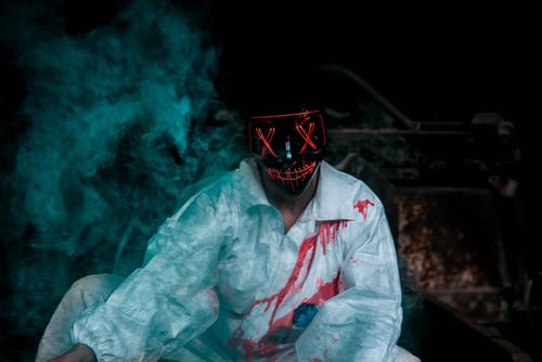 Man Wearing A Black Mask And Bloody Shirt