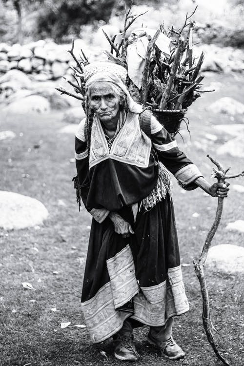 Grayscale Photography of Woman Carrying Branches