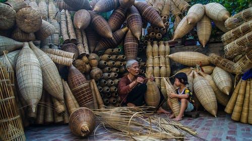 Woman Sitting Beside Girl Holding Brown Wicker Basket