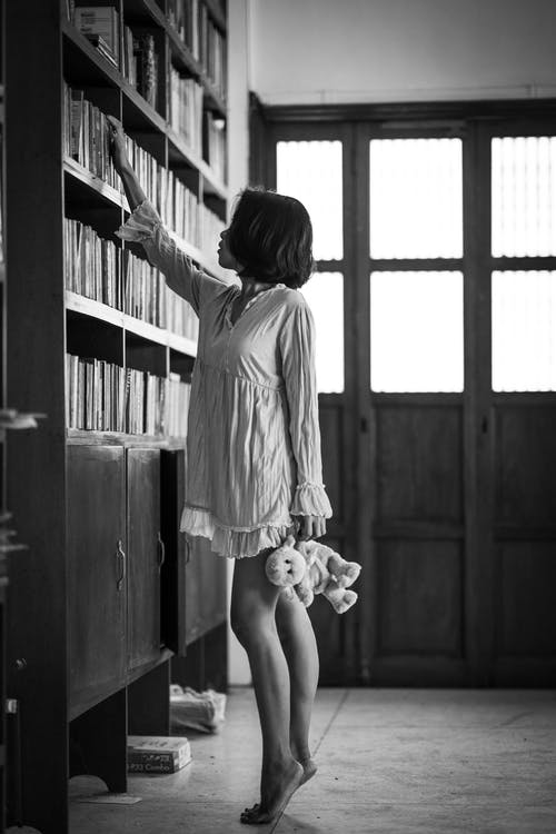 Monochrome Photo Of Woman Reaching For Book