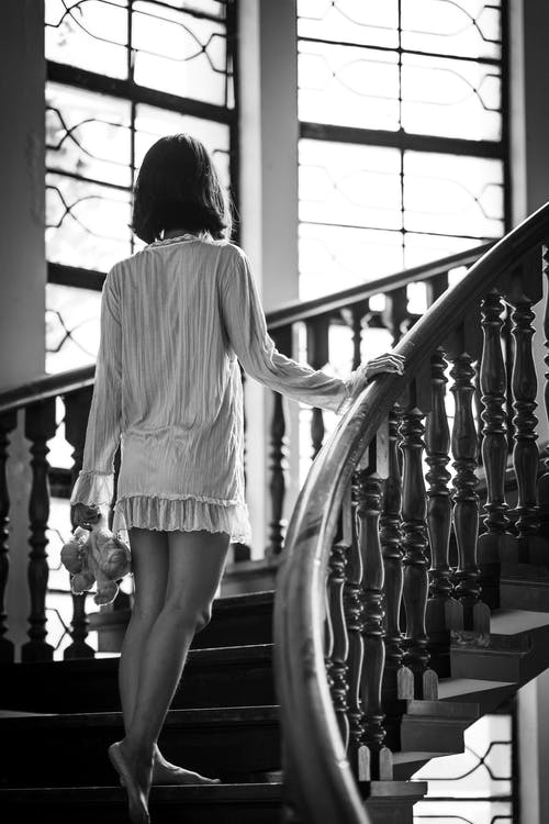 Monochrome Photo Of Woman Walking On Staircase