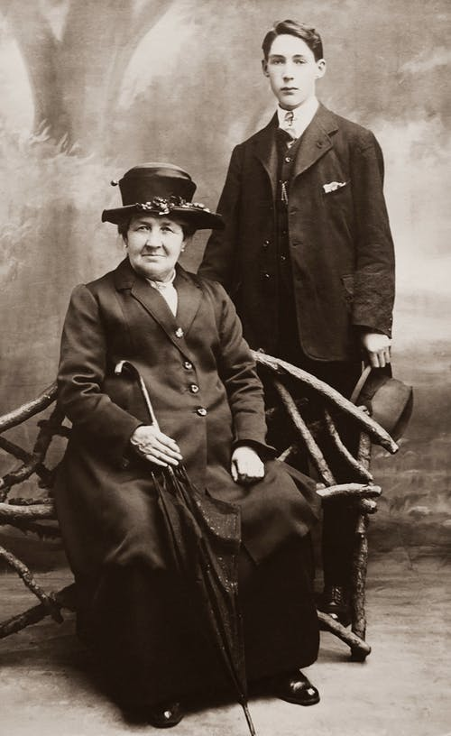 Man in Suit Standing Behind Sitting Woman Holding Umbrella