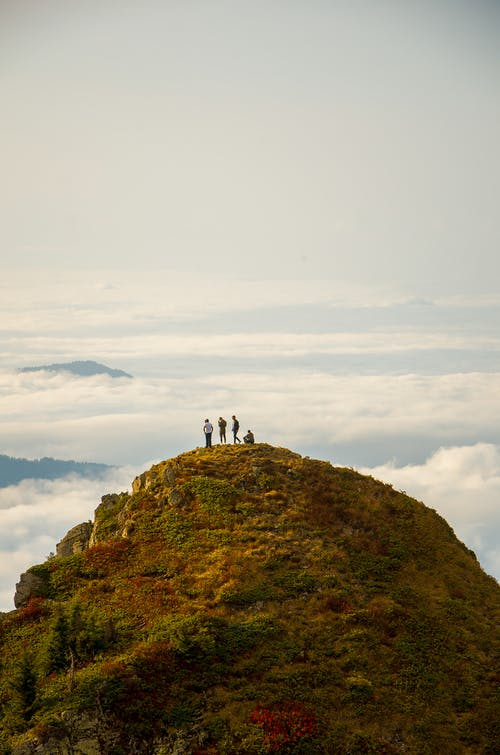 People Standing on Grass Mountain Top Near Clouds during Day