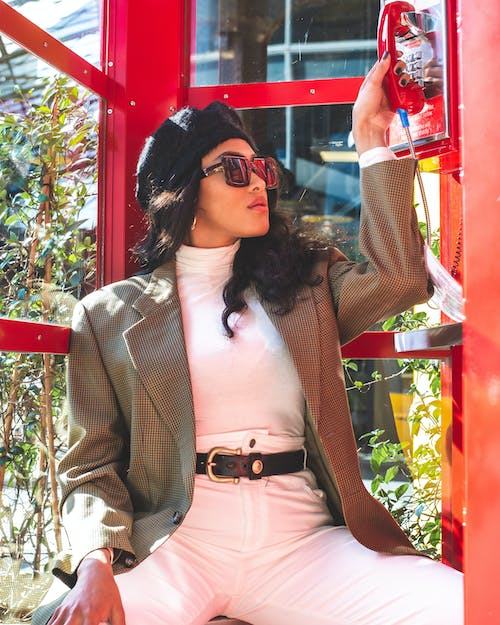 Photo Of Woman Sitting Inside Red Telephone Booth