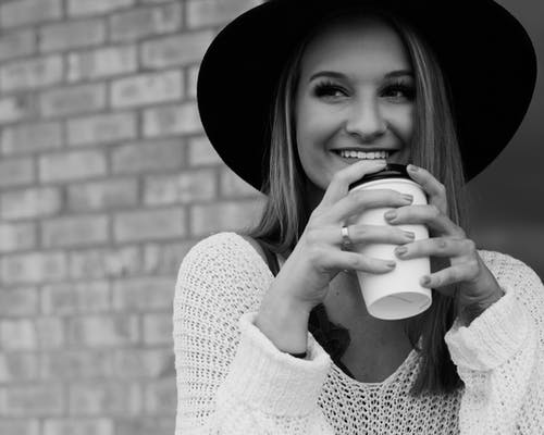 Happy young woman with takeaway coffee