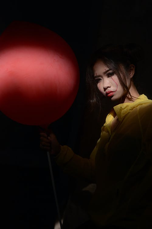 Woman Wearing Yellow Top Holding Red Balloon