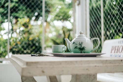 Teapot Beside Cup on Table
