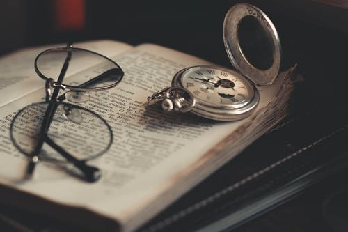 Round Silver-Colored Pocket Watch and Eyeglasses on Opened Book