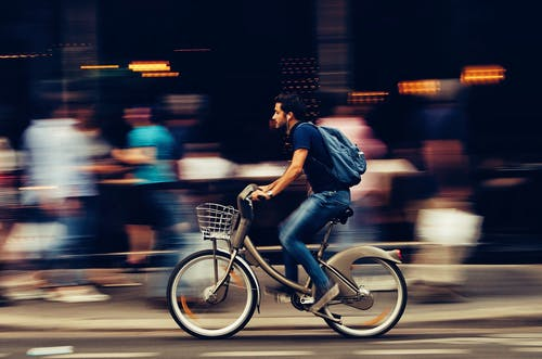Man Riding Bicycle on City Street