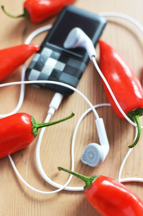 White Earphones Connected to Mp3 Player Surrounded by Red Chili Peppers
