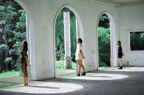Three Women Standing Beside Concrete Wall