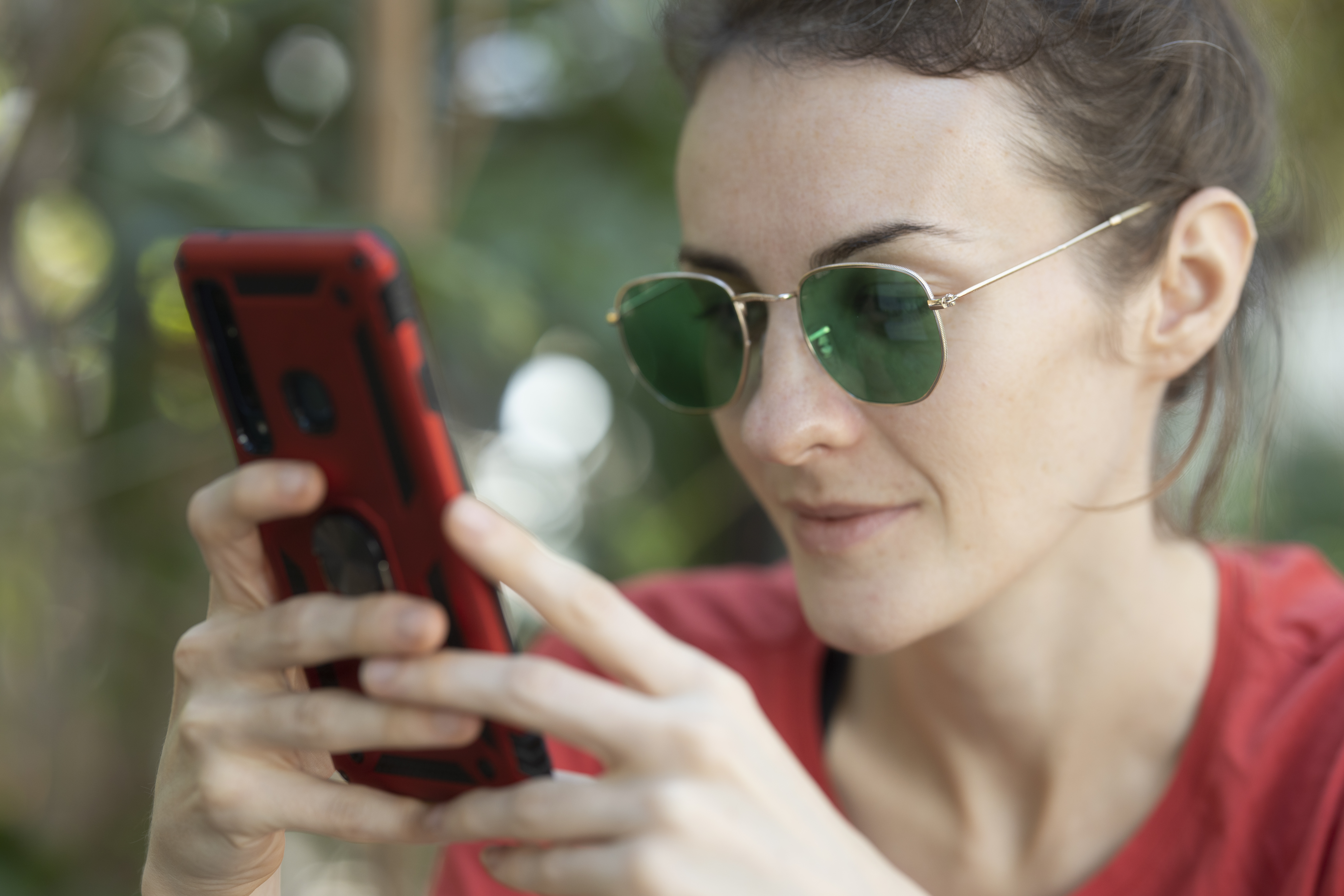 Woman Holding Smartphone and Wearing Sunglasses