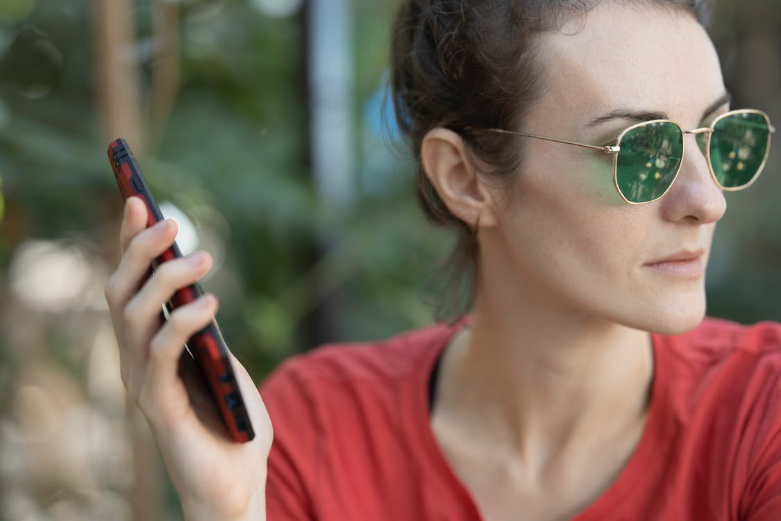 Woman in Red Top Wearing Sunglasses Holding Smartphone