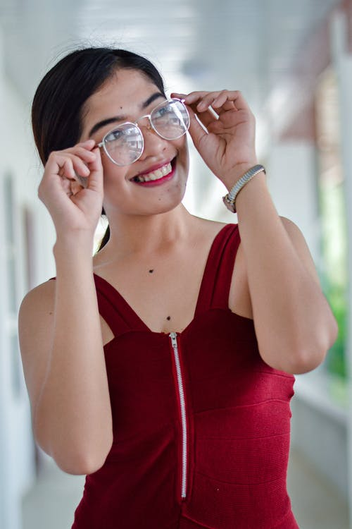 Woman Wearing Red Sleeveless Top While Holding Her Eyeglasses