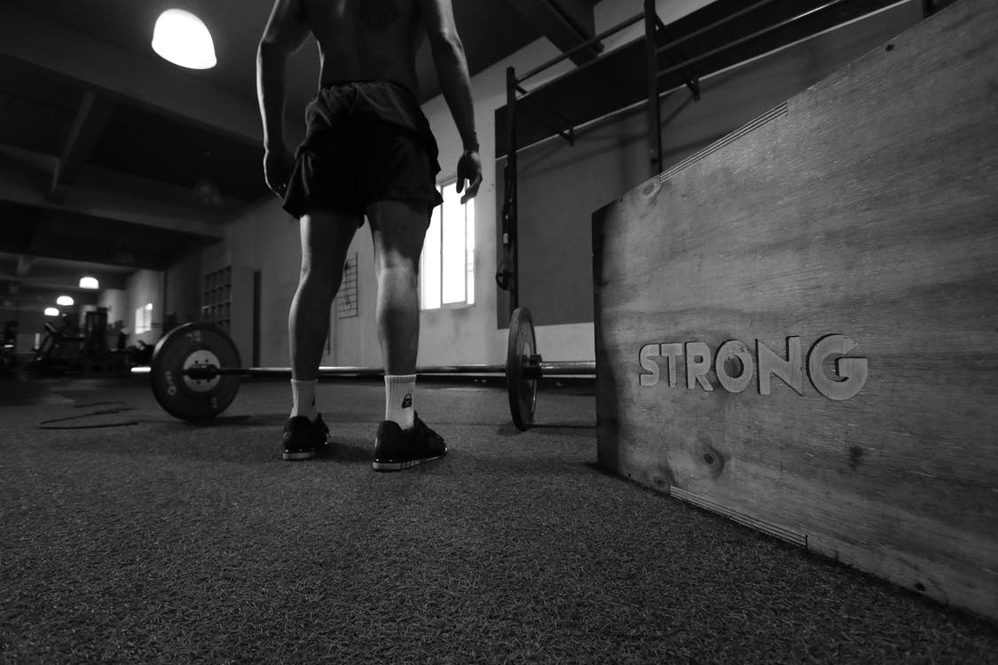 Grayscale Photo Of Man Standing Beside Barbell