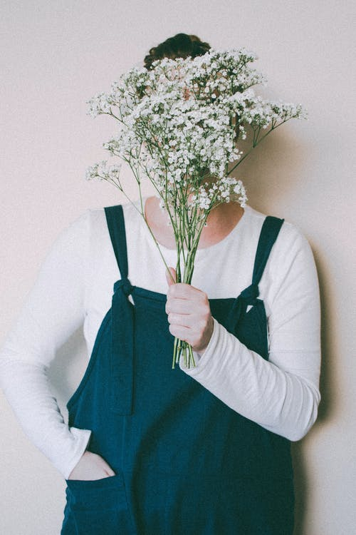 Person Hiding Face With Flowers