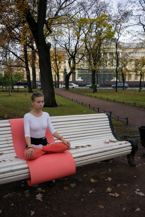 Woman Seated on Yoga Mat on Bench