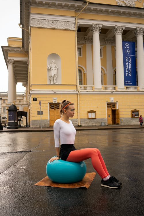 Woman Sitting on Fitness Ball in the Middle of the Street
