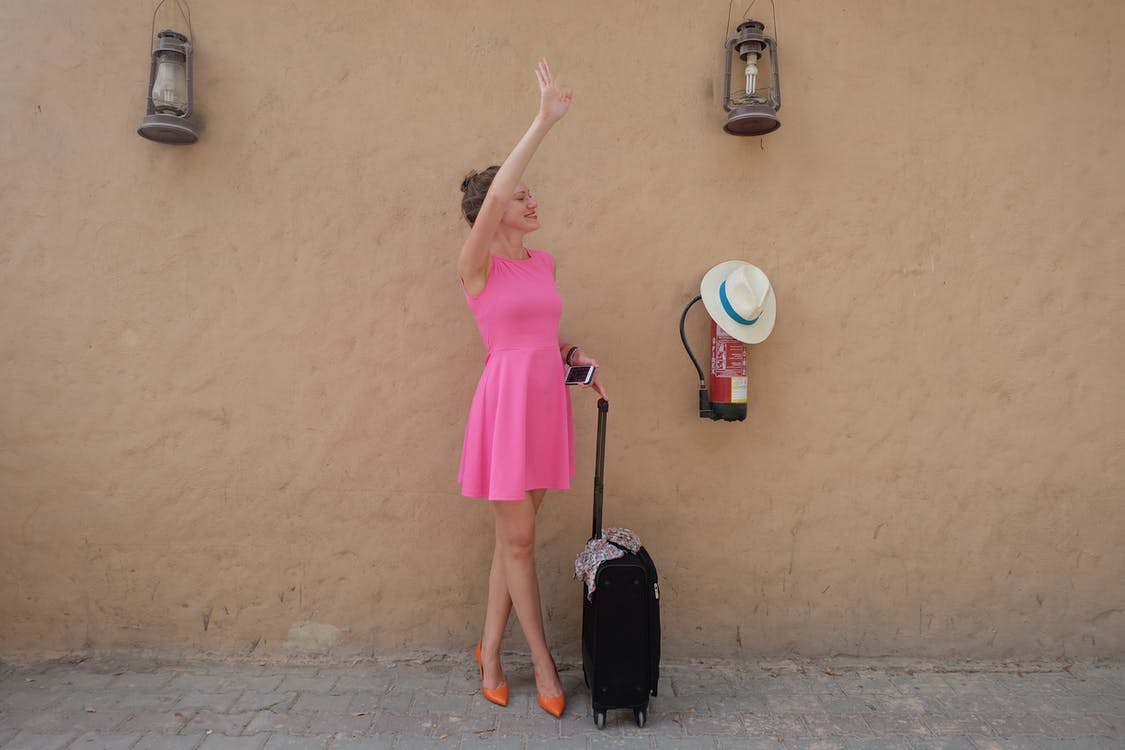 Woman Wearing Pink Sleeveless Dress Holding Luggage Bag While Waving Her Right Hand