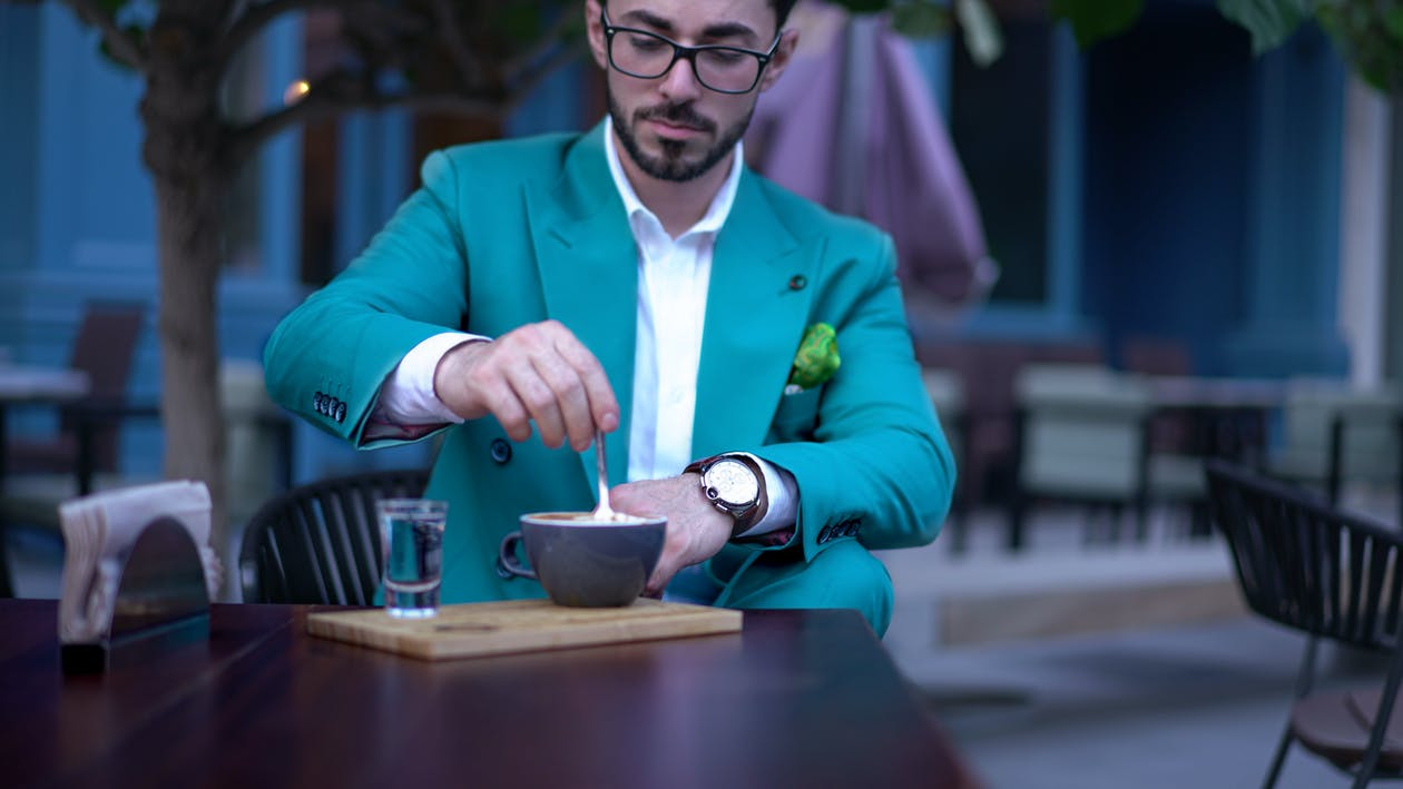 Man in Suit Stirring Hot Drink