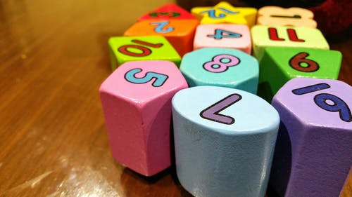 Assorted-color Dice Toy on Wooden Table
