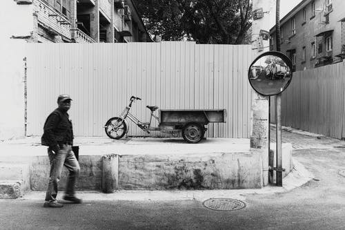 Grayscale Photo of Man Near Bicycle