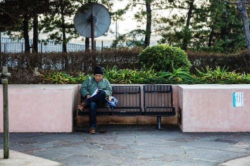 Man Sitting on Bench Using Mobile Phone