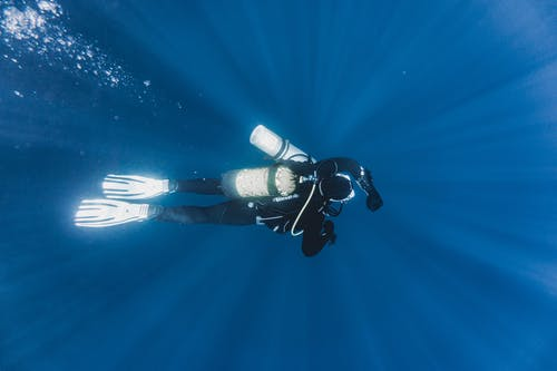 Unrecognizable diver swimming under sea water during travel