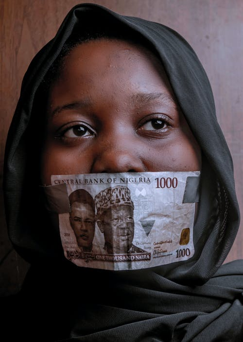 Woman Covering Her Mouth with 1000 Naira Note