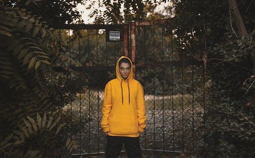 Person Wearing Yellow Hoodie Standing Beside Black Metal Gate