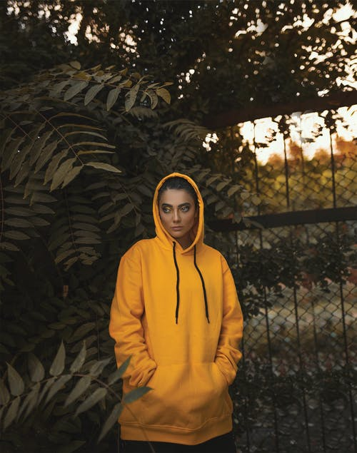 Woman in Yellow Hoodie Standing next to Plant