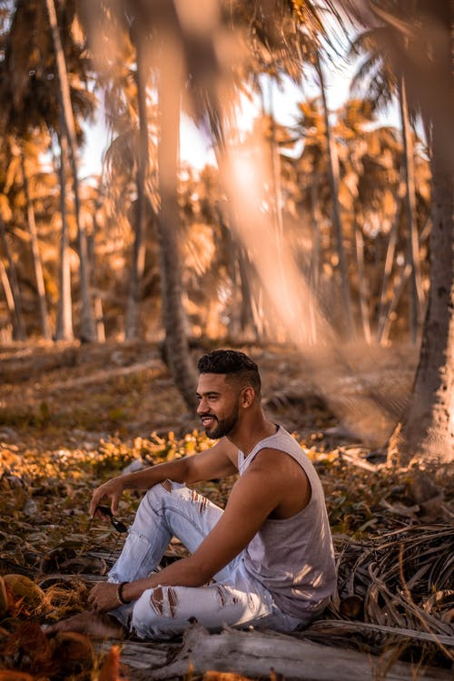 Man Sitting on Ground Surrounded by Palm Trees