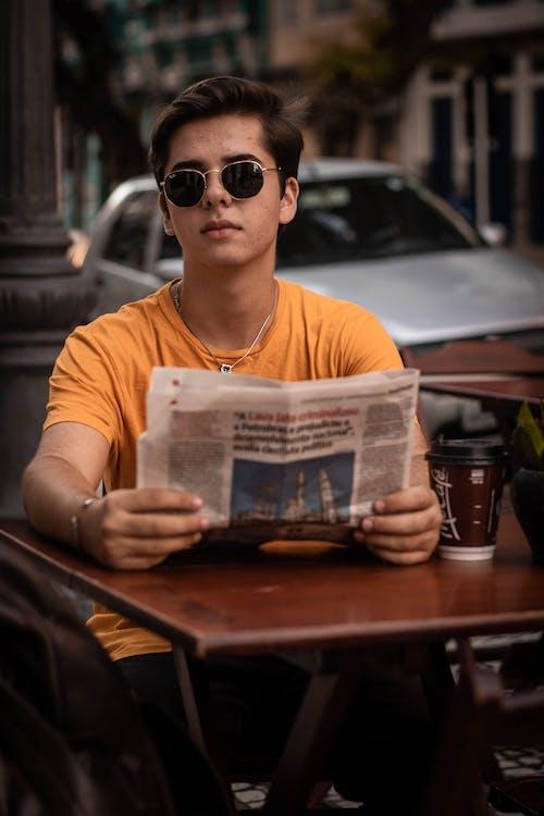 Man Wearing Yellow Crew-neck Shirt Holding Newspaper