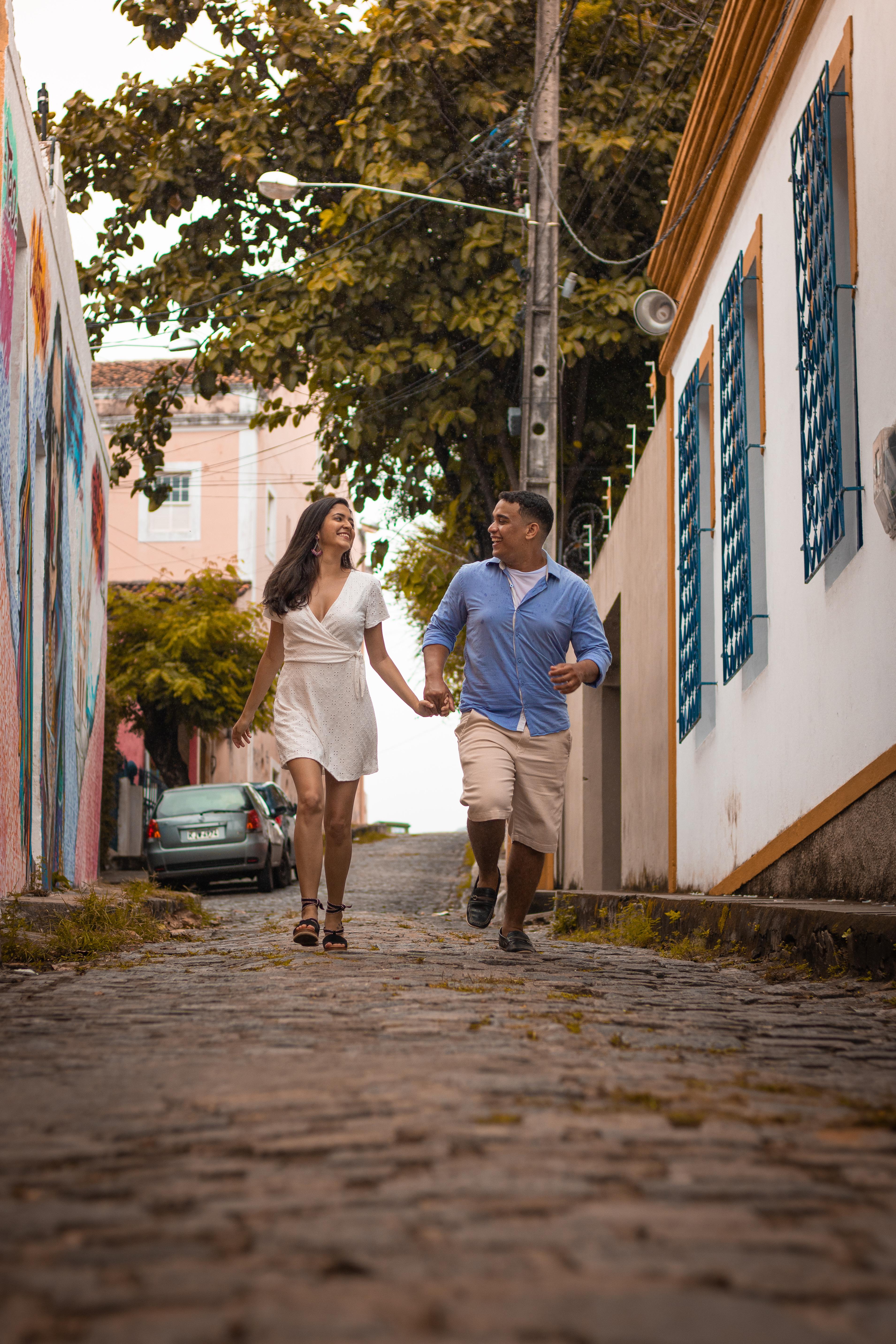 Woman Wearing White Dress Walking Beside of Man Wearing Blue Dress Shirt