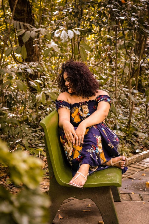 Woman in Purple, Yellow, and Green Floral Dress Sitting on Green Bench