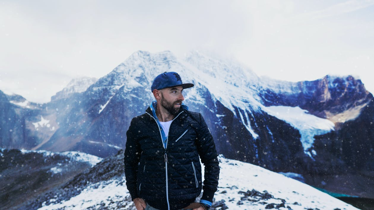 Photo of Man Standing Across Snow Capped Mountains