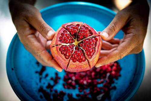 Close-up Photo of Person Holding Pomegranate Fruit