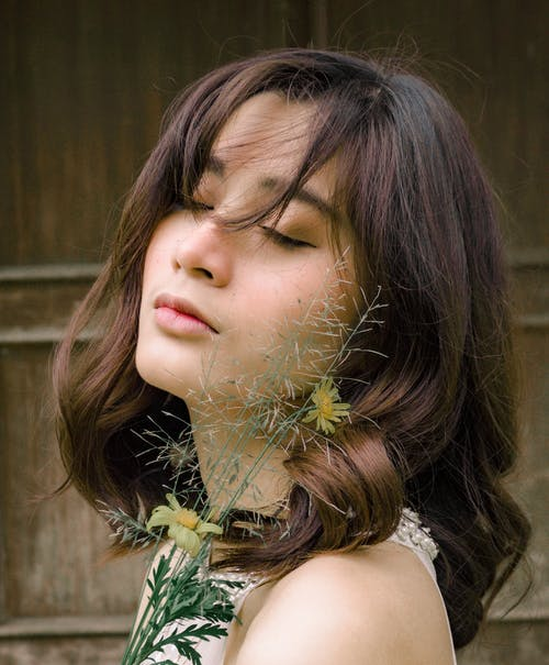 Side View Photo of Woman Posing With Her Eyes Closed Holding Flowers
