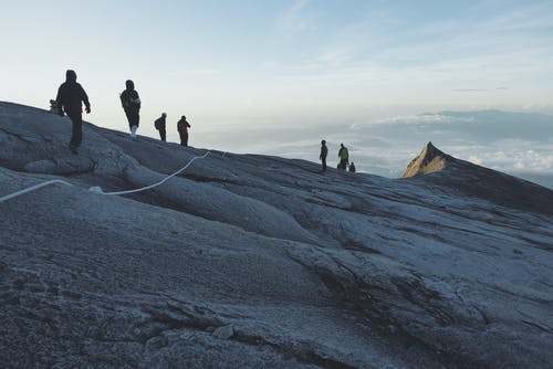 View Photography of People Climbing on Mountain