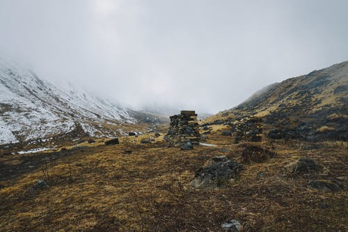 Low Angle Shot Of Piles Of Rocks On Withered Grounds Beside A Snow Capped Mountain With Dense Clouds