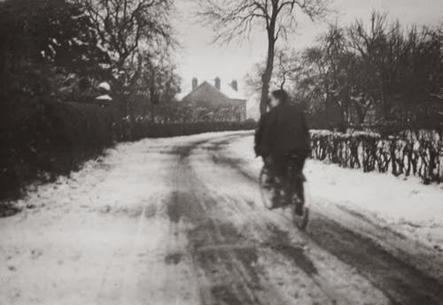 Grayscale Photography of Boys Riding a Bicycle On A Snow Covered Road