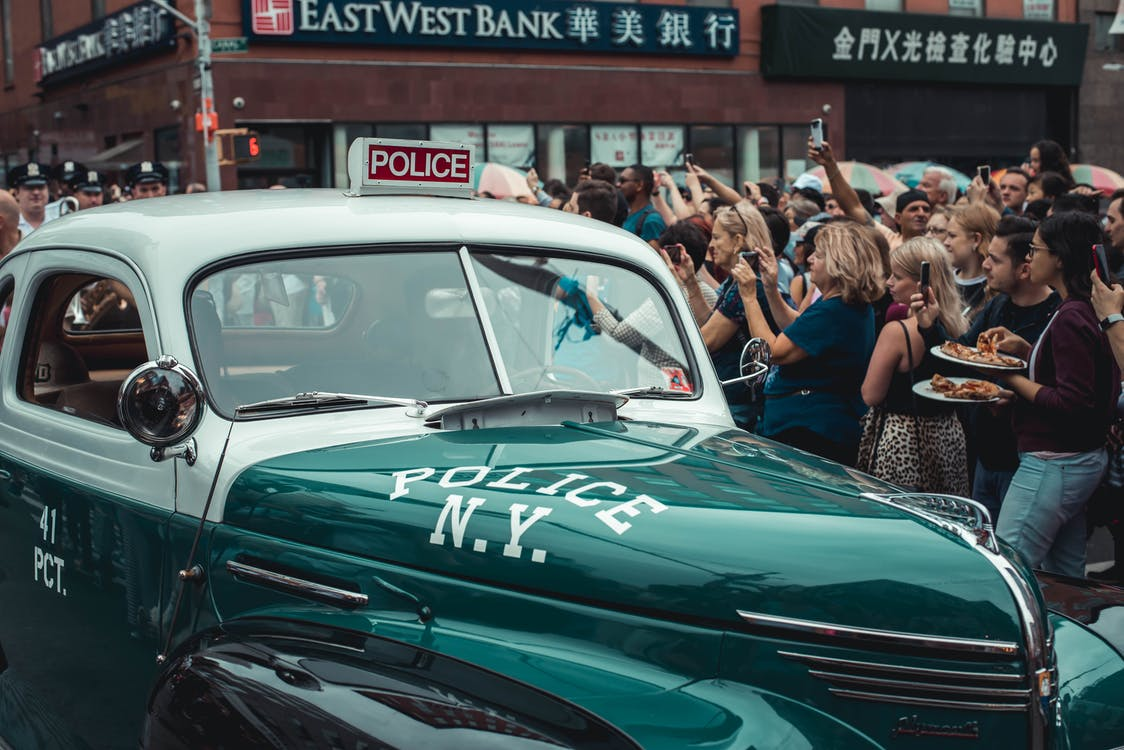 A Crowd Of People Gathered Around A Green Vintage Police Car In The City Street