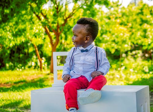 Boy Wearing Blue Shirt and Red Pants Sitting on Table