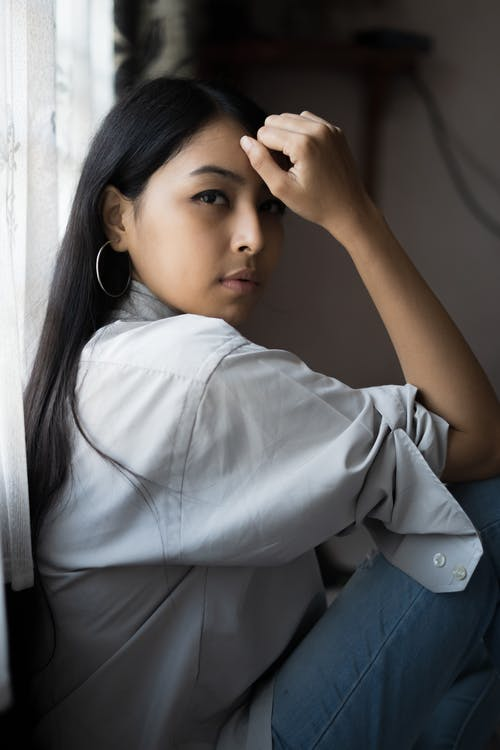 Side View Photo of Woman Sitting Beside Window Posing