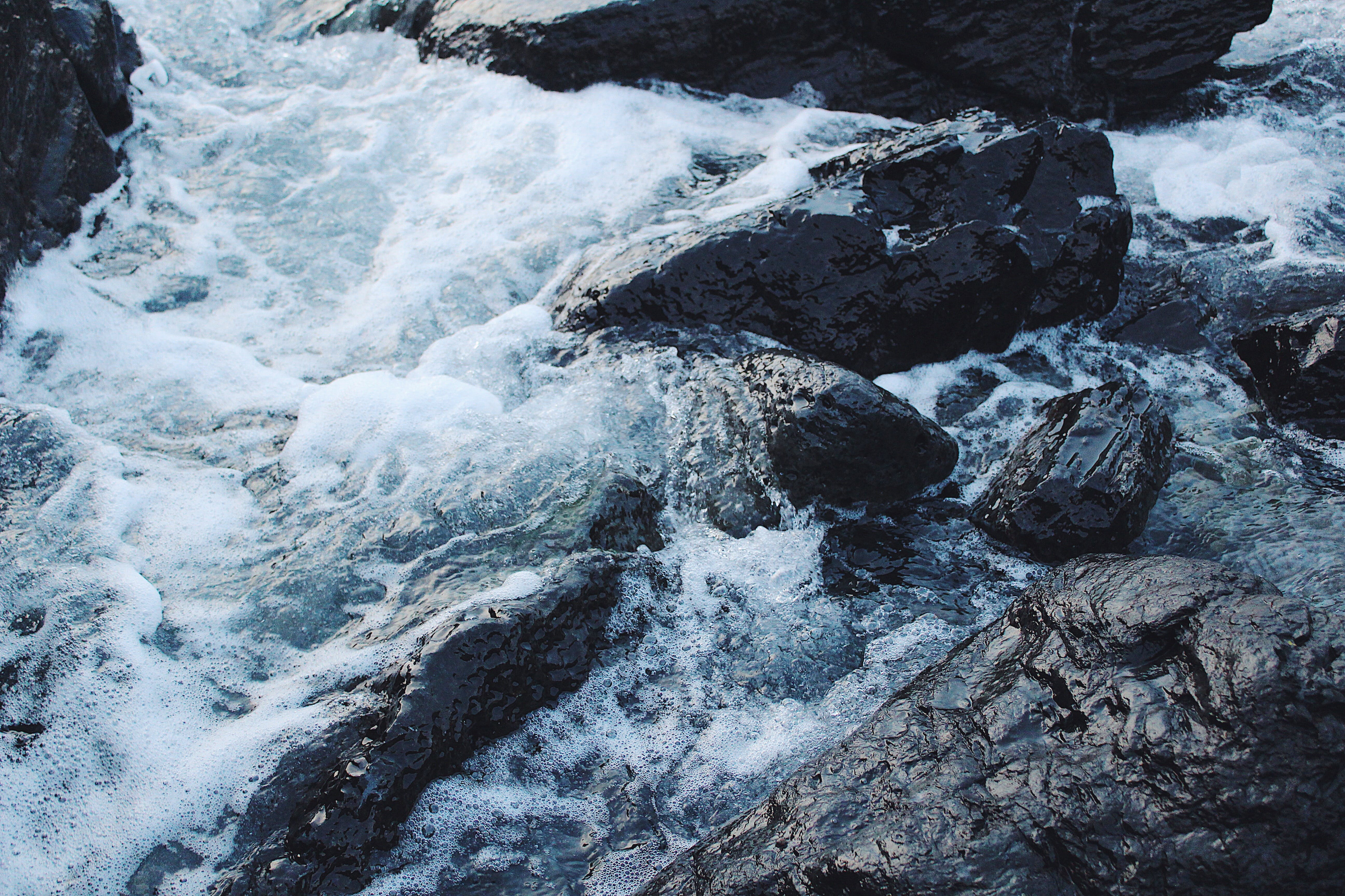High Angle Photo of Body of Water Splashing Against Gray Rocks