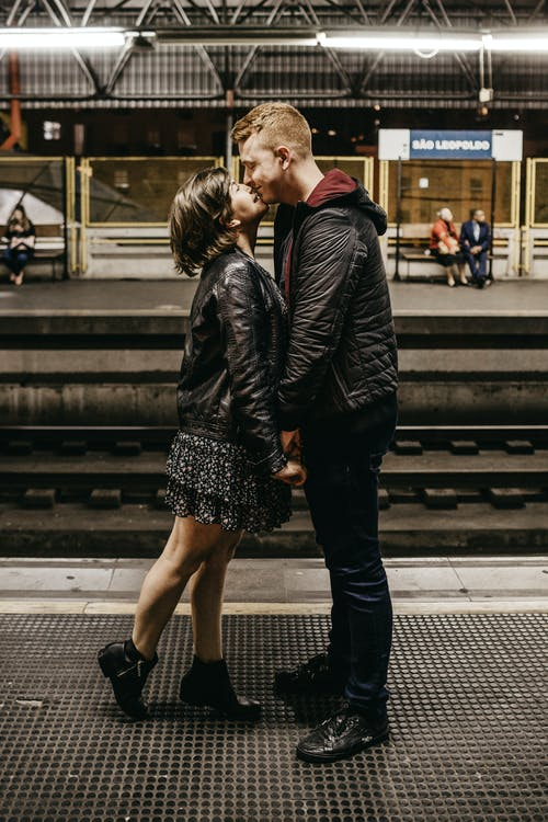 Photo of Couple Kissing While Standing on Train Station Platform